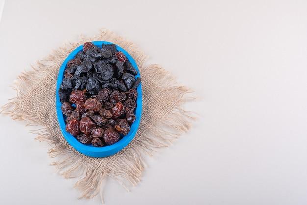 Blauw bord vol met gedroogde smakelijke pruimen op witte achtergrond. hoge kwaliteit foto