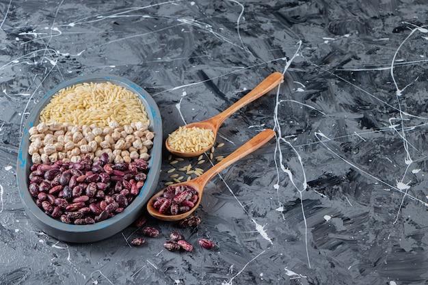Blauw bord vol rauwe kikkererwten, rijst en bonen op marmeren achtergrond.