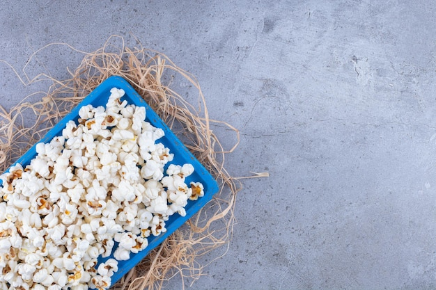 Blauw dienblad bovenop een stapel rietjes, gevuld met popcorn op marmeren oppervlak