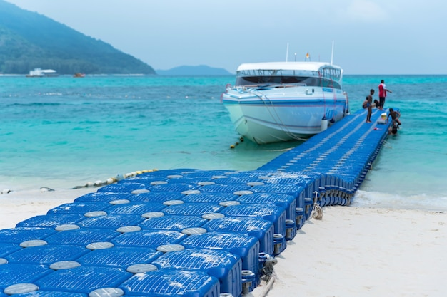 Blauw drijvend dok gemaakt van hdpe-kunststof. op de exotische blauwe zee met wit zandstrand tegen tropische bergen.