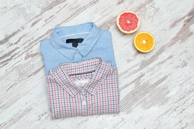 Blauw een geruit overhemd op een houten ondergrond en helften van citrusvruchten
