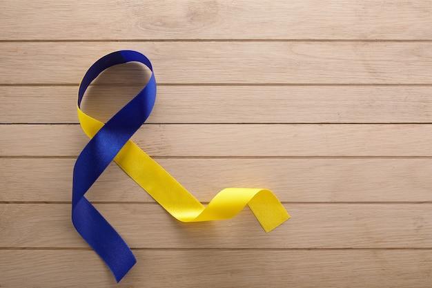 Blauw en geel lint op houten achtergrond. werelddag voor het downsyndroom. bewustzijn blauw lint.