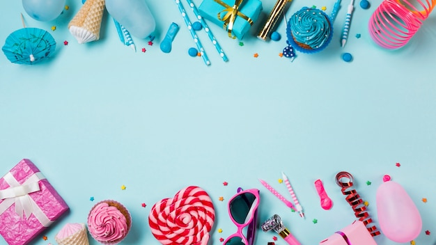 Blauw en roze gekleurde muffins; geschenkdozen; lolly; kaarsen; streamer en ballon op blauwe achtergrond