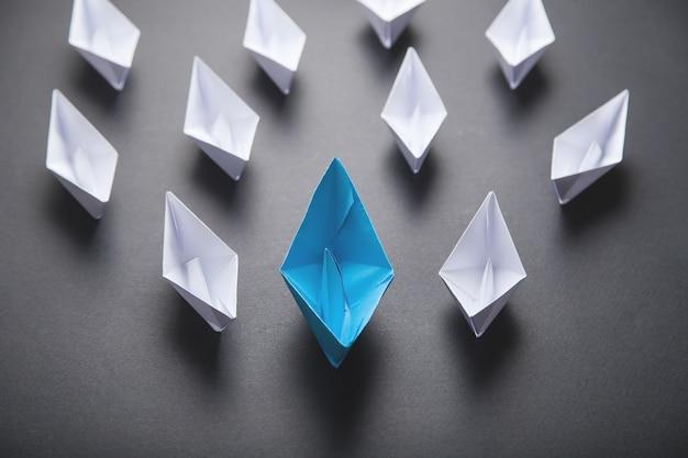 Blauw en wit papieren bootje. leiderschap concept