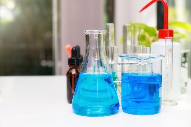 Blauw experimenteerwater in bekerglas en kolf in chemisch wetenschappelijk laboratorium.