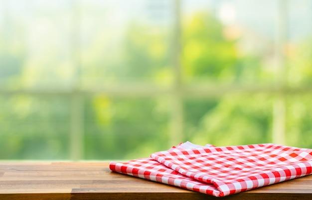 Blauw gecontroleerd tafelkleed op hout met groene bokeh van venster keuken achtergrond wazig.