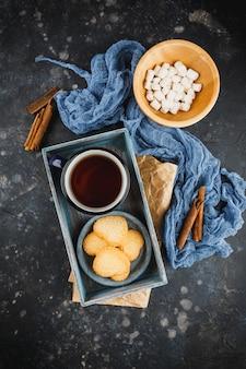 Blauw geëmailleerde kop thee, kaneelstokjes, anijssterren en zandkoekjes op zwart. bovenaanzicht.