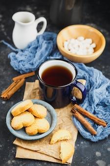 Blauw geëmailleerde kop thee, kaneelstokjes, anijssterren en zandkoekjes op zwart