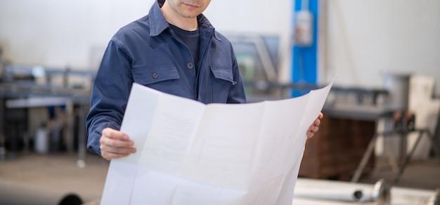 Blauw geklede ingenieur die een bluepringtekening leest in een industriële faciliteit. gezicht niet zichtbaar