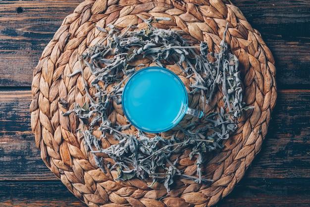 Blauw gekleurd water in een onderzetter met thee bovenaanzicht op een donkere houten achtergrond