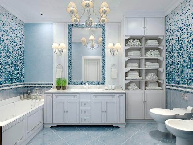 Blauw gekleurde badkamer met wit meubilair en grote spiegel met schansen en luxe kroonluchter.