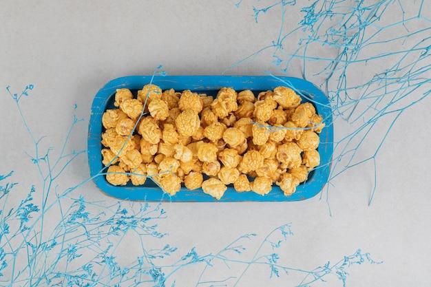 Blauw gekleurde takken rond een kleine, blauwe schotel met karamelpopcorn op marmeren tafel.