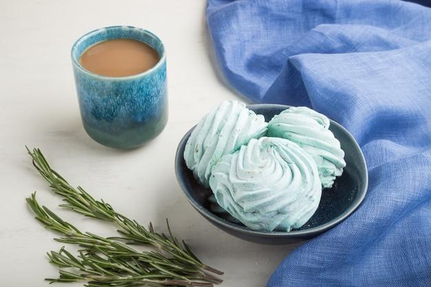 Blauw gekleurde zelfgemaakte zephyr of marshmallow met kopje koffie op witte houten oppervlak met blauw textiel