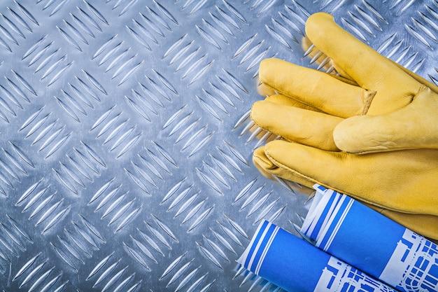 Blauw gerolde technische tekeningen lederen beschermende handschoenen op co