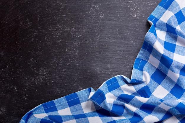 Blauw geruit tafelkleed op donkere tafel, bovenaanzicht met kopie ruimte