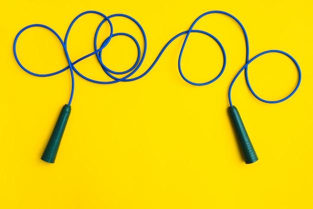 Blauw geschiktheidstouwtjespringen om met plastic handvatten op gele achtergrond te springen