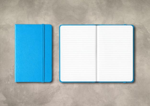 Blauw gesloten en open bekleed notitieboekjemodel dat op concrete achtergrond wordt geïsoleerd