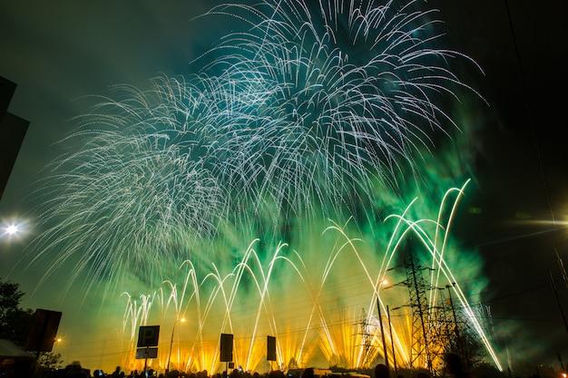 Blauw, groen en geel feestelijk vuurwerk. internationaal vuurwerkfestival rostec
