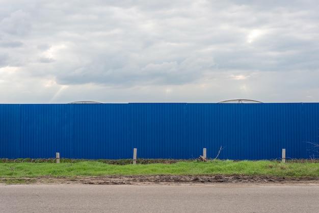 Blauw hek met bomen in de buurt van de weg. voorjaar 2021.