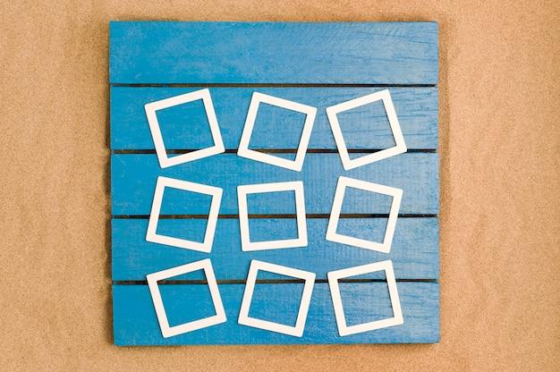 Blauw hout en zeezand met frames voor foto's. bovenaanzicht