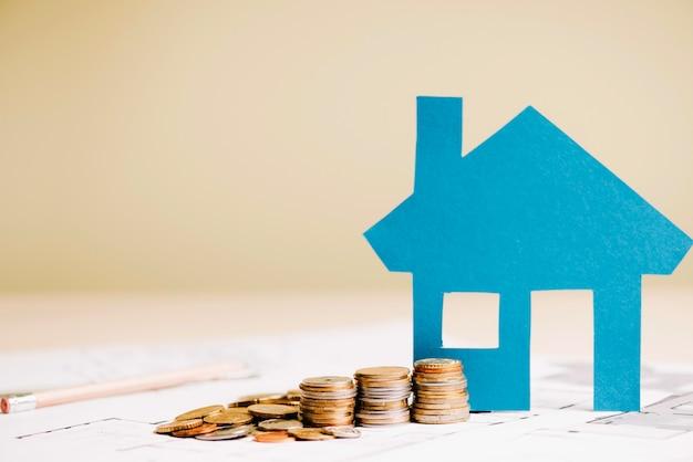 Blauw huis en munten op blauwdruk