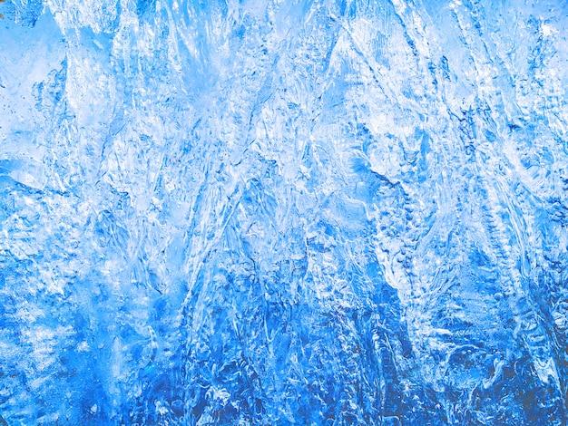Blauw ijs gestructureerde achtergrond met ruw oppervlak. bevroren water met kristallen