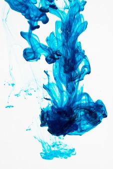 Blauw inktdruppeltje in water verspreiden