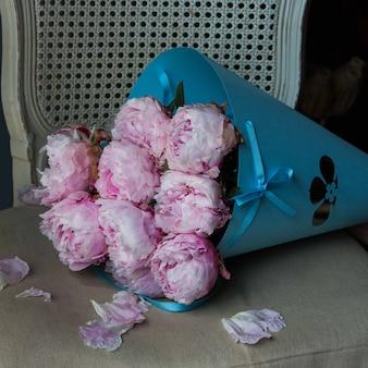 Blauw kartonnen boeket van roze pioenrozen op een stoel.