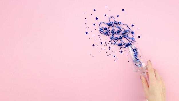 Blauw klatergoud in een glas op roze exemplaar ruimteachtergrond en hand