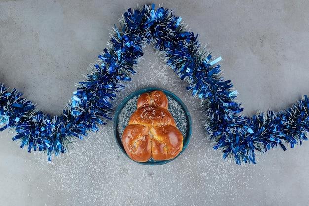 Blauw klatergoud in een zigzag naast een zoet broodje op marmeren tafel.