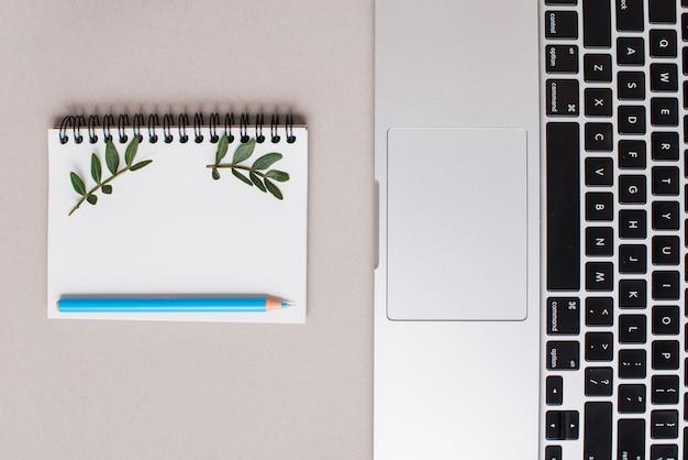 Blauw kleurpotlood op spiraalvormige blocnote en laptop op grijze achtergrond