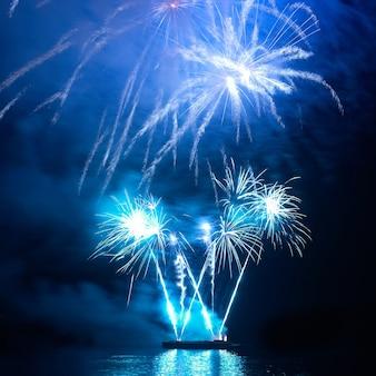Blauw kleurrijk vakantievuurwerk op de zwarte hemelachtergrond.