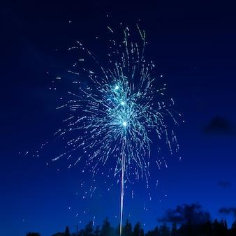 Blauw kleurrijk vuurwerk op de achtergrond van de nachthemel