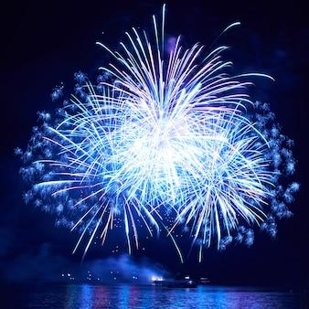 Blauw kleurrijk vuurwerk op de zwarte hemelachtergrond
