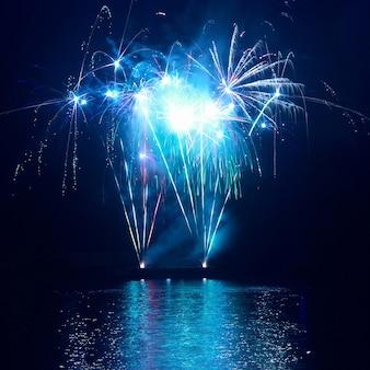 Blauw kleurrijk vuurwerk op de zwarte lucht