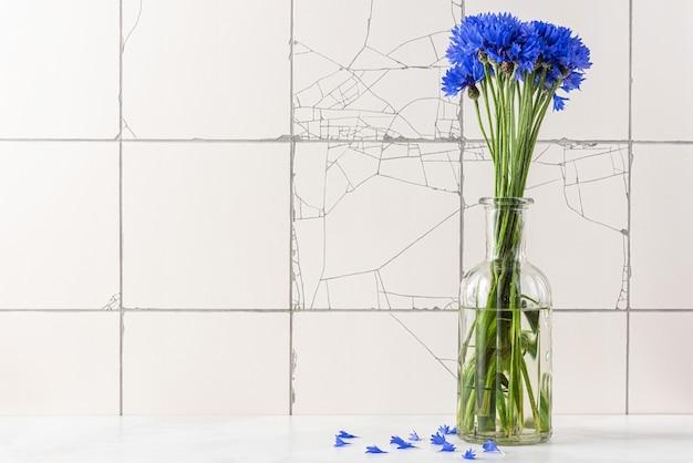 Blauw korenbloemenboeket in vaas op wit rustiek tegeloppervlak