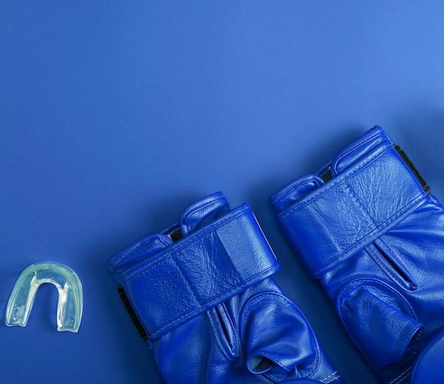Blauw lederen bokshandschoenen en siliconen kap voor tanden