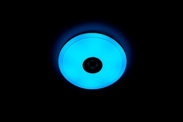 Blauw licht led plafondlamp met ingebouwde draadloze speakers op zwarte achtergrond.