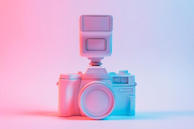 Blauw licht op vintage geschilderde roze camera tegen roze achtergrond