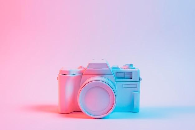 Blauw licht over een oude vintage camera over roze oppervlak geschilderd