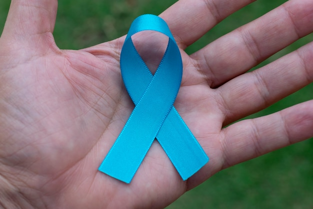 Blauw lint in iemands handpalm. blauwe november. prostaatkanker preventie maand. de gezondheid van mannen.