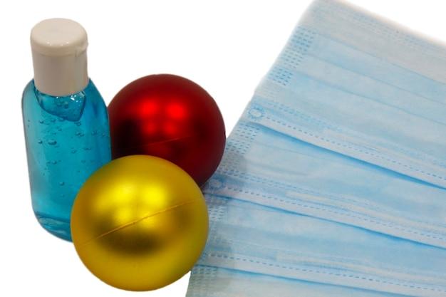 Blauw medisch masker naast kerstversiering op een witte achtergrond. kerstbomen, ballonnen, nieuwjaarsstemming en ademhalingsbescherming