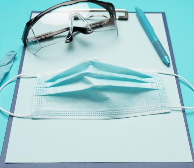 Blauw medisch wegwerpmasker op een blauwe achtergrond, close-up persoonlijke beschermingsmiddelen voor de luchtwegen tegen virale infecties