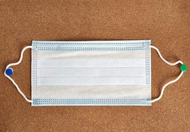 Blauw medisch wegwerpmasker op een bruine achtergrond, persoonlijke beschermingsmiddelen voor de luchtwegen tegen virale infecties, bovenaanzicht