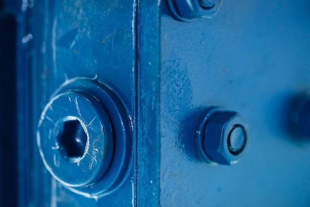 Blauw metalen ruw oppervlak van onderdeel met bouten en moeren