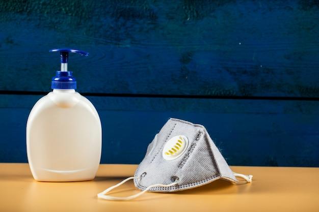 Blauw modern gezichtsmasker met een witte ontsmettingsmiddelcontainer die op oranje muur wordt geïsoleerd