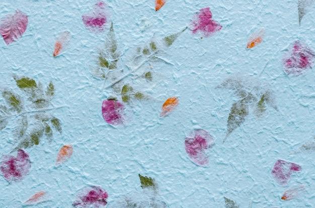 Blauw moerbeiboomdocument met bloemblaadje en bladtextuurachtergrond.