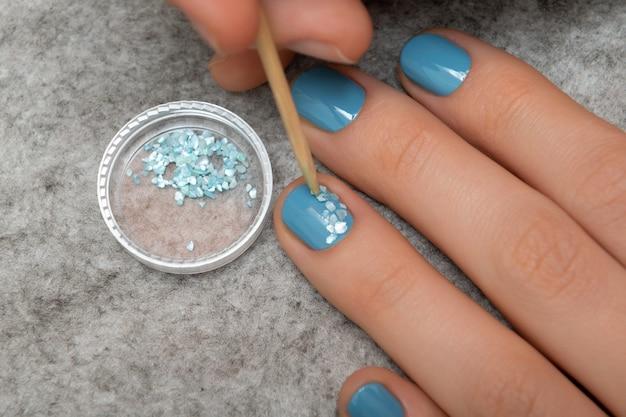Blauw nagelontwerp. gemanicuurde vrouwelijke hand