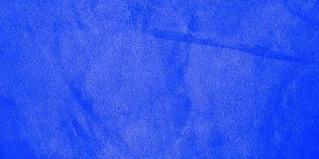 Blauw natuurlijk suède als achtergrond met een donkere rand en een licht midden. horizontale webbanner.
