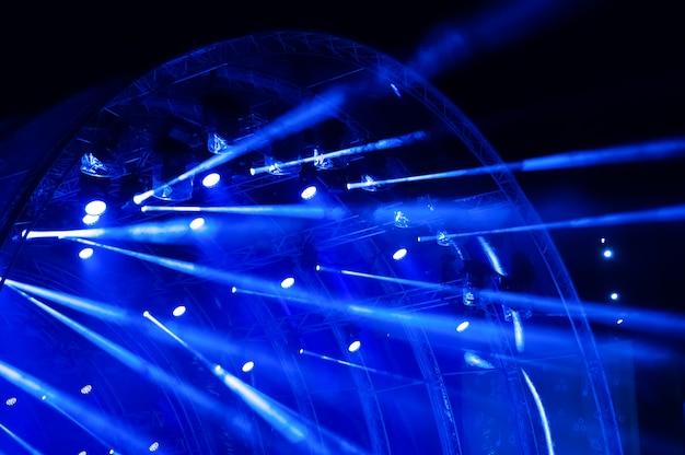 Blauw neonlicht. lichtstralen van concertverlichting op een donkere achtergrond boven het projectiescherm.